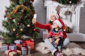 Matka a dcera v Santa klobouky přičemž selfie v blízkosti slavnostní borovice doma