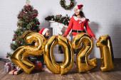 Dcera a matka v Santa klobouky stojící za balónky s čísly