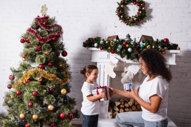 Side view of mother and daughter with gifts looking at each other at home