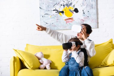 Mother pointing with finger and daughter using virtual reality headsets at home stock vector
