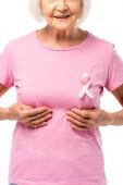 Partielle Ansicht einer älteren Frau, die ihre Brust isoliert auf Weiß berührt, Konzept des Brustkrebses