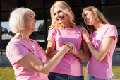 Three women in pink t-shirts standing together, looking at each other outdoors