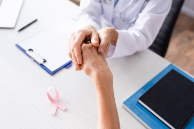 Selective focus of doctor holding patient hand near pink ribbon on table stock vector