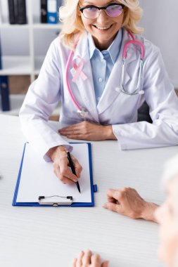Selective focus of doctor writing on clipboard and looking at patient in clinic stock vector