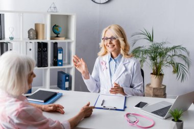 Selective focus of doctor talking to patient while sitting at workplace stock vector