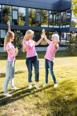 Excited three women in pink t-shirts with ribbons of breast cancer awareness