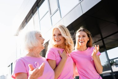 Women in pink t-shirts laughing and hugging outdoors, concept of breast cancer stock vector