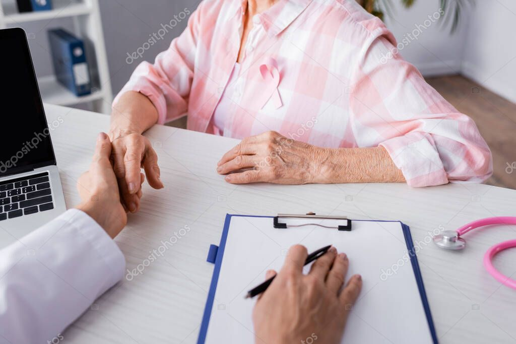 Cropped view of doctor holding patient hand near laptop and clipboard stock vector