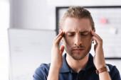 Müder Büroangestellter mit geschlossenen Augen berührt Kopf mit Händen am Arbeitsplatz auf verschwommenem Hintergrund