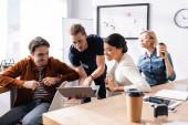 mladý podnikatel ukazuje na notebook poblíž multietnických podnikatelů, kteří spolupracují