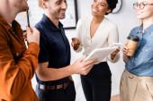 veselý podnikatel držící digitální tablet poblíž usmívajících se multikulturních kolegů
