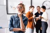 Blonde Manager, die wegsehen, und multiethnische Kollegen, die auf verschwommenem Hintergrund kommunizieren
