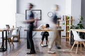 vyčerpaná africká americká obchodnice spící na stole v otevřeném prostoru kanceláře, rozostření pohybu