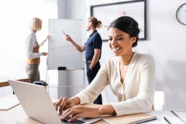 Smiling african american woman typing on laptop while sitting at workplace with blurred colleagues working on background stock vector