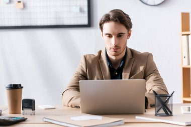 Focused office worker looking at laptop, while sitting at desk with stationery in office on blurred background stock vector