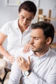 Masseuse massaging aching shoulder of businessman in office on blurred background