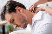 Detailní pohled masérky masírující krk vousatého podnikatele na rozmazaném pozadí