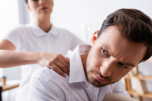 Close up view of serious businessman looking away while masseuse massaging shoulders on blurred background