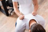 Ausgeschnittene Ansicht der Masseurin bei Rückenmassage für Klient im Büro auf verschwommenem Hintergrund