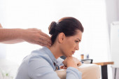 Side view of masseur massaging painful neck of brunette businesswoman on blurred background