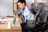 Glas Wasser und Medikamente auf dem Tisch mit verschwommener Geschäftsfrau mit verletztem Rücken im Hintergrund