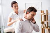 Női masszázs terapeuta masszírozás fáj nyak üzletember ül masszázs szék homályos háttér