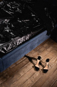 Photo High heeled shoes on floor near bed with black bedding