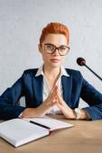 Összpontosított vörös hajú nő ujjbegyek megható gesztus, félrenéz, miközben ül az asztalnál a tanácsteremben