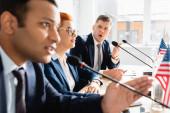 Zaklatott politikus nyitott szájjal nézi a mikrofonban beszélő kollégát, miközben a tárgyalóteremben ül a homályos előtérben.