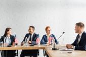 Politiker zu zweit betrachten einander, während sie sich während einer Parteiversammlung im Sitzungssaal unterhalten