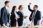 Boldog multikulturális politikusok nézik izgatott csapatvezető kéz a kézben a levegőben a kongresszuson