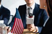 ostříhaný pohled na korespondenta s mikrofonem při rozhovorech s politikem během stranického kongresu, rozmazané popředí