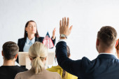 political agitator pointing with hand at man with raised hand on blurred background