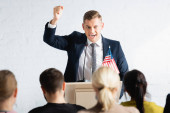 vzrušený řečník ukazující vítězné gesto při rozhovoru s agitátory v konferenčním sále, rozmazané popředí