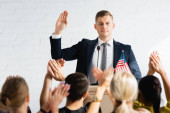confident candidate showing swear gesture in front of applauding voters in conference room