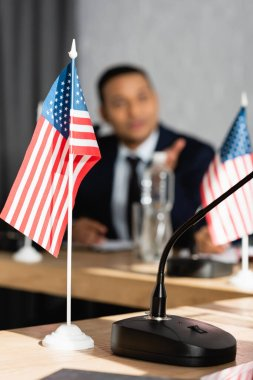 Small american flag with microphone on table with blurred indian man on background