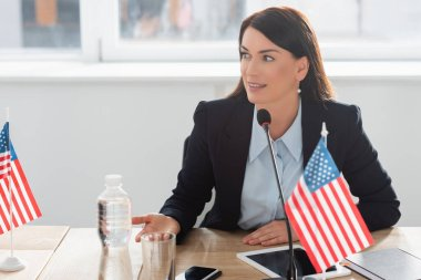 Smiling woman in formal wear looking away, while speaking in microphone, sitting near american flags in boardroom