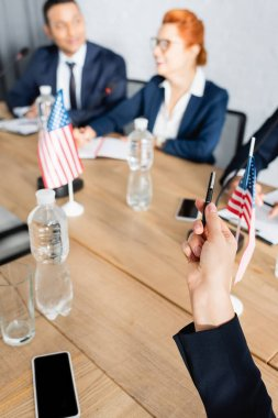 Man pointing with pen, while sitting in boardroom with blurred interracial colleagues