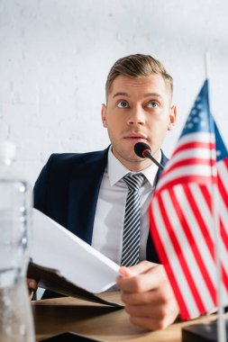 Confident member of political party holding clipboard, while speaking in microphone at table with usa flag on blurred foreground