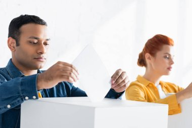 Multicultural electors inserting ballots into polling boxes on blurred background stock vector