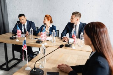 multiethnic politicians talking during party congress while sitting at desk with usa flags