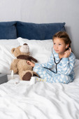 Photo child playing while examining teddy bear with stethoscope while playing in bed