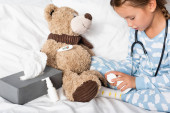 dívka otevření pilulky láhev při hraní s medvídkem v ložnici