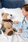 dívka vytvrzování medvídek při hraní v posteli