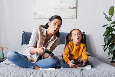 KYIV, UKRAINE - SEPTEMBER 15, 2020: shocked woman with daughter sitting with crossed legs and playing video game stock vector
