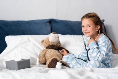 Cheerful child looking at camera while examining teddy bear with stethoscope stock vector