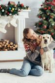 šťastná žena ve svetru sedí na podlaze a mazlí labrador u vánočního stromku