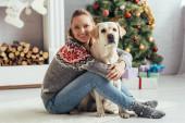 šťastná žena ve svetru sedí na podlaze s labrador v blízkosti zdobené vánoční stromeček