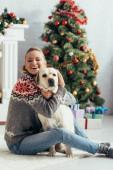 boldog nő csukott szemmel ül a padlón, és átöleli labrador közel karácsonyfa