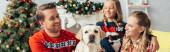 Fotografie glückliche Familie in Pullovern beim Blick auf Labrador neben geschmücktem Weihnachtsbaum, Banner